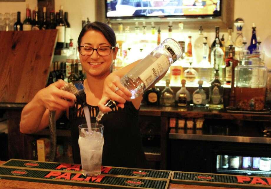 Head bartender Aria Minigiello prepares a drink inside the bar at Little Pub Wilton, 26 Danbury Road. Photo: Stephanie Kim / Hearst Connecticut Media
