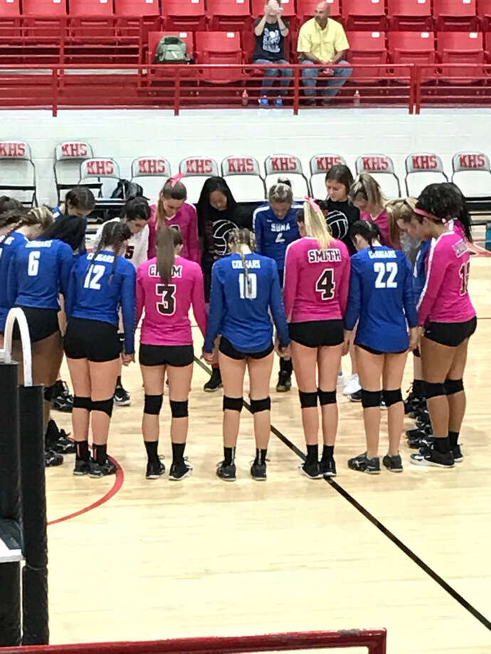 Members of the Kirbyville and Buna high school volleyball teams pray after a game official suffered chest pains and was flown to a hospital by helicopter. (Photo provided by Tommy Wallis)
