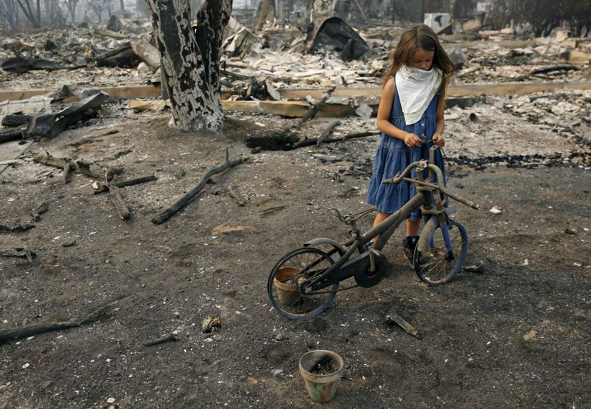Arilyn Edwards, 6, stands beside her bike in front of the rubble of her Santa Rosa home on Tuesday, Oct. 10, 2017. The bike, which was a gift for her 6th birthday on Oct. 6, was destroyed as fire ripped through her neighborhood early Monday morning.