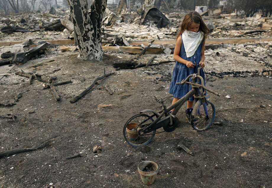 Arilyn Edwards, 6, stands beside her bike in front of the rubble of her Santa Rosa home on Tuesday, Oct. 10, 2017. The bike, which was a gift for her 6th birthday on Oct. 6, was destroyed as fire ripped through her neighborhood early Monday morning. Photo: Guy Wathen/The Chronicle