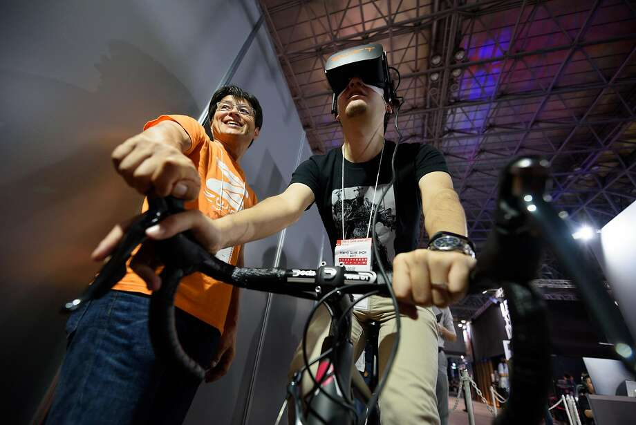 An attendee wearing an Oculus VR headset rides on a cycle simulator at the Tokyo Game Show 2017 in September. Facebook, which owns Oculus, now hopes to jumpstart sales with a cheaper, standalone headset. Photo: Akio Kon, Bloomberg