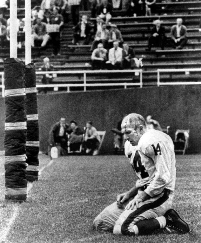 In this 1964 photo, New York Giants quarterback Y.A. Tittle kneels after being sacked by the Pittsburgh Steelers in Pittsburgh. Tittle, the Hall of Fame quarterback and 1963 NFL Most Valuable Player, has died. He was 90. (Morris Berman/Pittsburgh Post-Gazette via AP) Photo: Morris Berman / Associated Press / Pittsburgh Post-Gazette