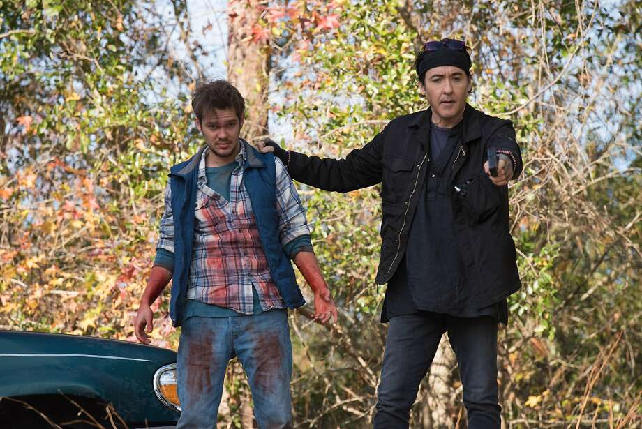 """A weirdly attired lowlife criminal (John Cusack, right) menaces a river rafter (Ellar Coltrane) in """"Blood Money."""" Photo: Saban Films"""