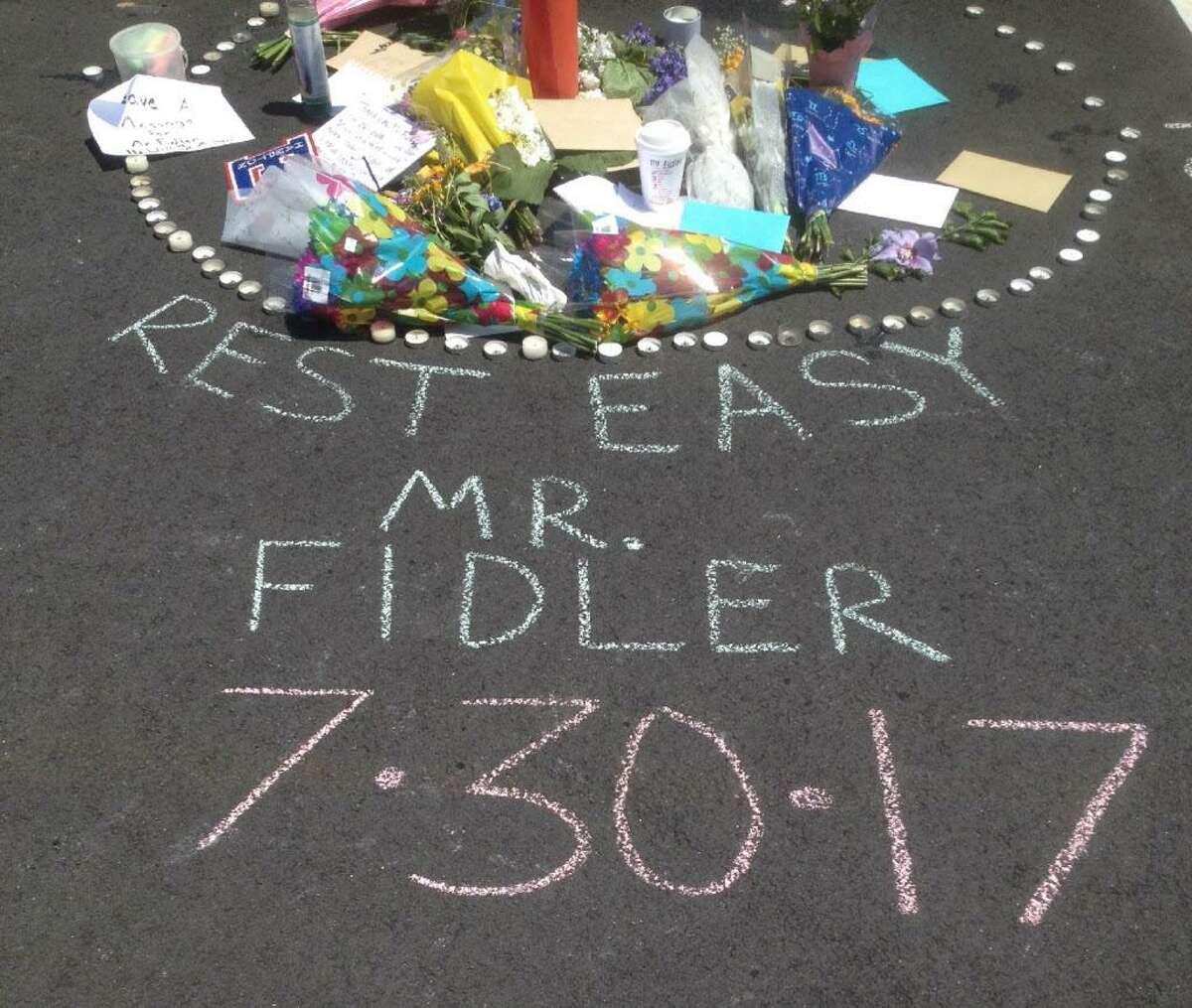 A chalked tribute to East Hampton High School Principal John Fidler marks his parking spot.