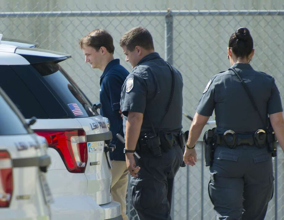 Matthew Alexander Naquin, left, one of the LSU chapter Phi Delta Theta fraternity members booked at LSU Police Dept. headquarters Wednesday, Oct. 11, 2017, on charges related to the Sept. 14 death of one of the fraternity's pledges, freshman Matthew Gruver, 18, is escorted from the building by LSU Police Dept. officers before being driven to East Baton Rouge Parish Prison. Ten members were charged with hazing, and one, Naquin, was additionally charged with negligent homicide. Photo: ADVOCATE STAFF PHOTO BY TRAVIS SPRADLING/The Advocate