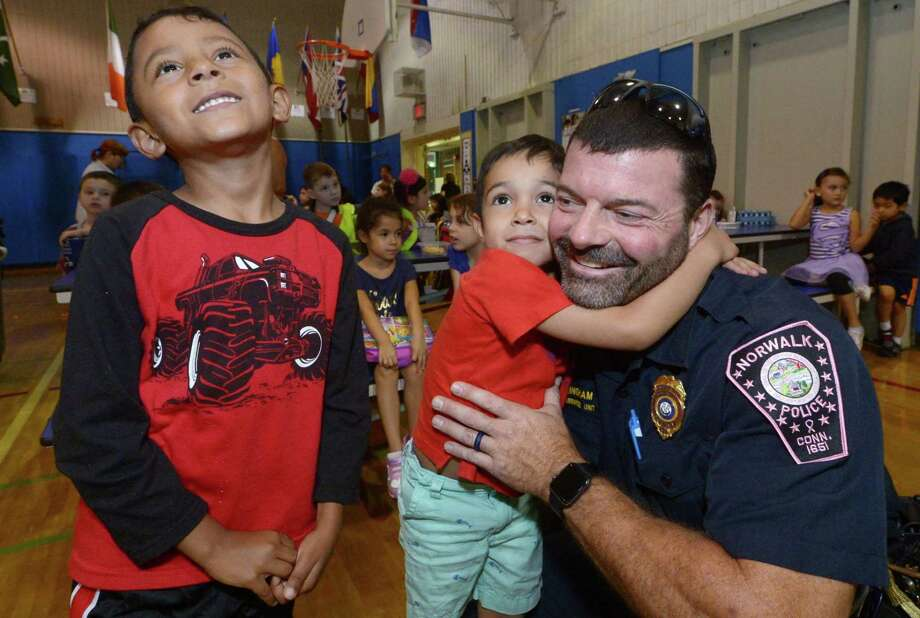 Norwalk Police Lieutenant Brian Cunningham gets a hug from Christopher Cuxum as Alfredo Folgar waits his turn as Silvermine Dual Language Magnet School holds a Police and First Responders Luncheon Tuesday, October 9 2017, to have an opportunity for students to interact with officers, firefighters and paramedics at the school in Norwalk, Conn. Photo: Erik Trautmann / Hearst Connecticut Media / Norwalk Hour