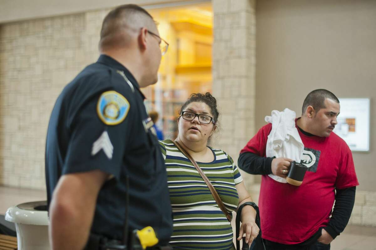 Midland Police Sgt. Chris Wenzell, left, chats with Reva Martinez, center, and Christopher Martinez, right, both of Midland, during a