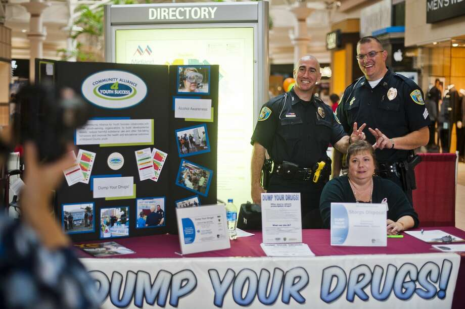 """Midland Police Community Relations Officer Paul McDonald, left, and Sgt. Chris Wenzell, right, stick up bunny ears behind Michelle Beeck, a prevention specialist with the Legacy Center, as Barb Swierzbin, a prevention services coordinator with the Legacy Center, left, takes a photo during a """"Dump Your Drugs"""" event on Wednesday at the Midland Mall. The event allows people to drop off their expired and unwanted prescriptions and also serves to promote the 24-hour secure drop box located at the Law Enforcement Center. (Katy Kildee/kkildee@mdn.net) Photo: (Katy Kildee/kkildee@mdn.net)"""