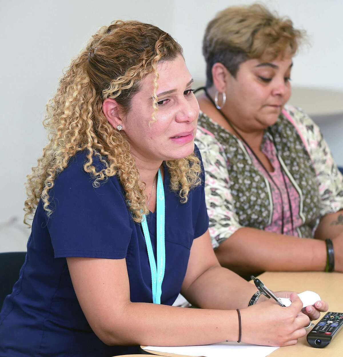 Kelly Rivera, left, talks about her parents' situation in Anasco, Puerto Rico, at the Fair Haven Community Health Center Wednesday in New Haven, where she works. At right is Carmen Camacho.