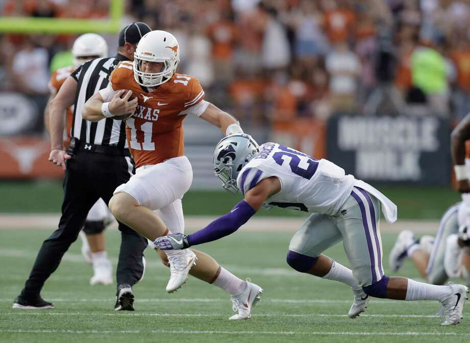 FILE - In this Oct. 7, 2017, file photo, Texas quarterback Sam Ehlinger (11) runs around Kansas State defensive back Denzel Goolsby (20) during the first half of an NCAA college football game, in Austin, Texas. With a tough running style that break tackles and drives defensive backs to the ground, Texas freshman quarterback Sam Ehlinger is sending a message to rival Oklahoma: these Longhorns are tougher than Texas teams of recent past past. (AP Photo/Eric Gay, File) Photo: Eric Gay, STF / Copyright 2017 The Associated Press. All rights reserved.