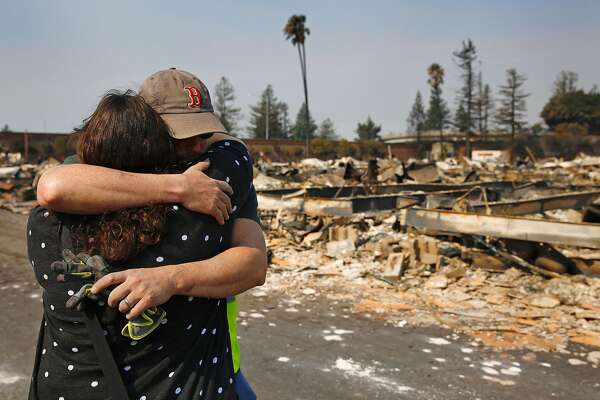 Family members embrace at a destroyed home containing the remains, they believe, of their family member at Journey's End mobile home park Oct. 11, 2017 in Santa Rosa, Calif.