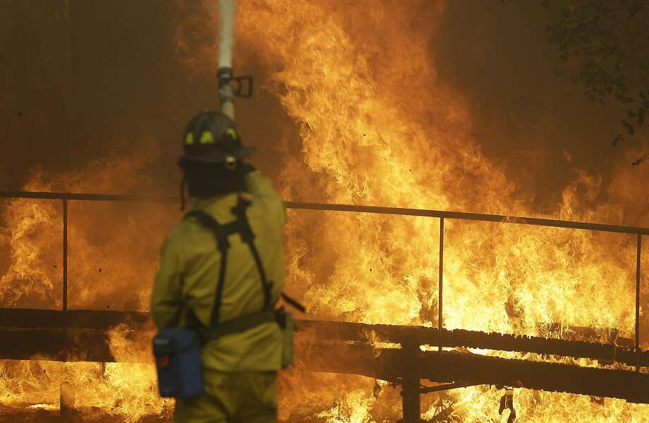 A firefighter battles flames Monday at Keysight Technologies in Santa Rosa. The company said most of its headquarters are intact, but some workers lost homes. Photo: Jeff Chiu, Associated Press