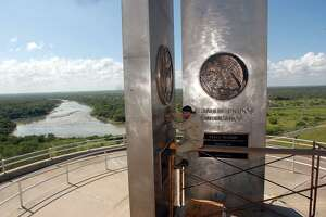 STATE - Jesus Angel Juarez cleans the U.S. and Mexico monuments on the borderline on Falcon Dam on Friday, Oct. 17, 2003. The dam was completed 50 years ago. The Rio Grande flowing out of the dam can be seen in the background. BILLY CALZADA / STAFF