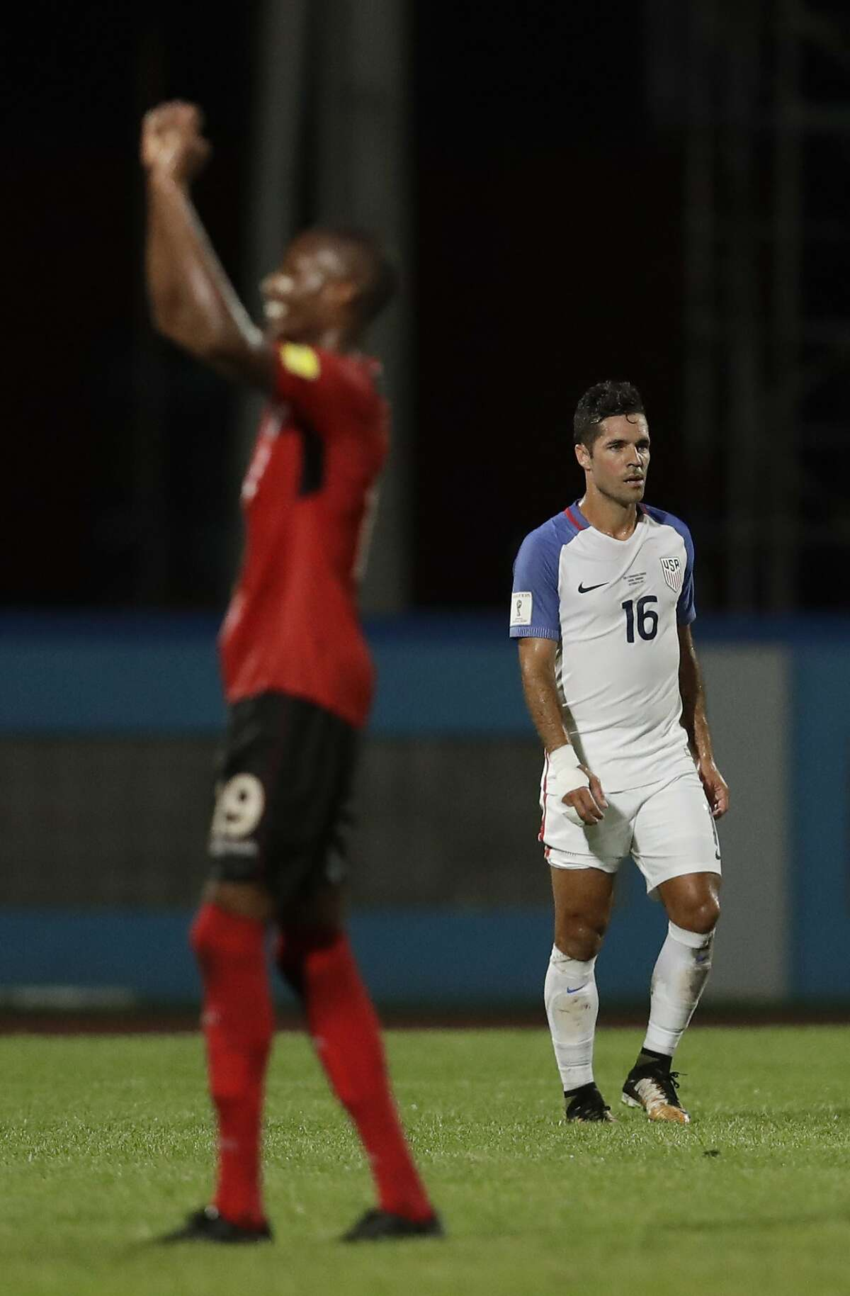 United States' Benny Feilhaber, right, walks off the field as Trinidad and Tobago's Kevan George celebrates defeating the U.S. in their final World Cup qualifying match at Ato Boldon Stadium in Couva, Trinidad and Tobago, Tuesday, Oct. 10, 2017. (AP Photo/Rebecca Blackwell)