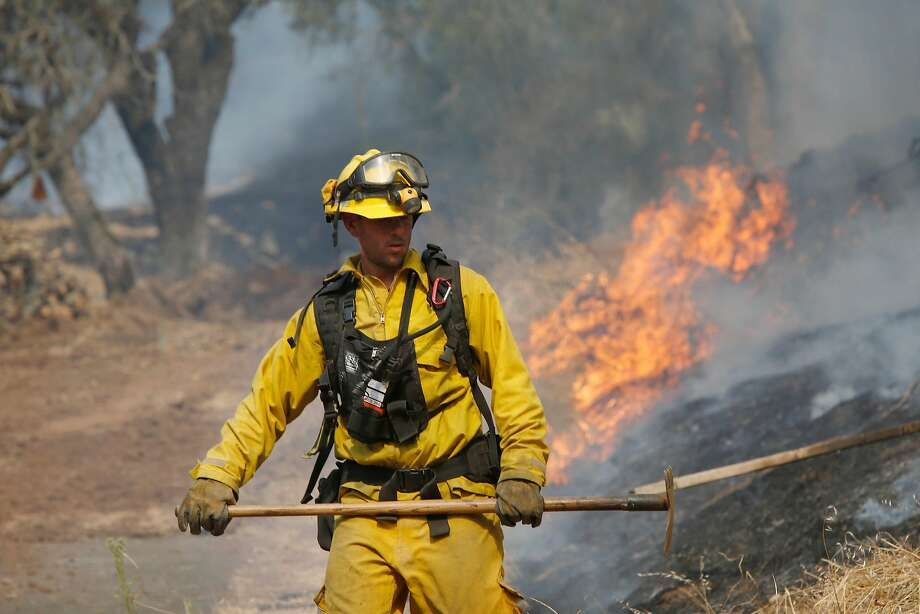 A firefighter works to control a fire  near a bulldozer line created behind homes along Bennett Valley Road as he and other firefighters monitor it 's progress on Wednesday, October 11, 2017 in Santa Rosa, Calif. Photo: Lea Suzuki, The Chronicle