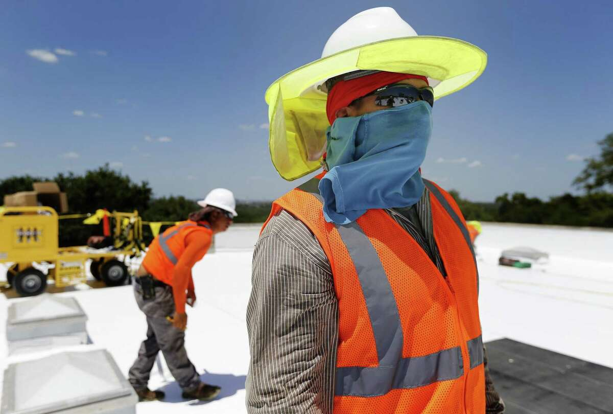 Isaac Cruz Saucedo protects himself from extreme sun exposure as Beldon Roofing workers take on a job at Sunshine Cottage during the heat of the day in 2017. When climate scientists look at how global warming will change San Antonio, one clear signal emerges: An already-hot city is going to get hotter. By 2040 to 2060, nearly every day of an average July or August will be above 100 degrees, according to one computer model.