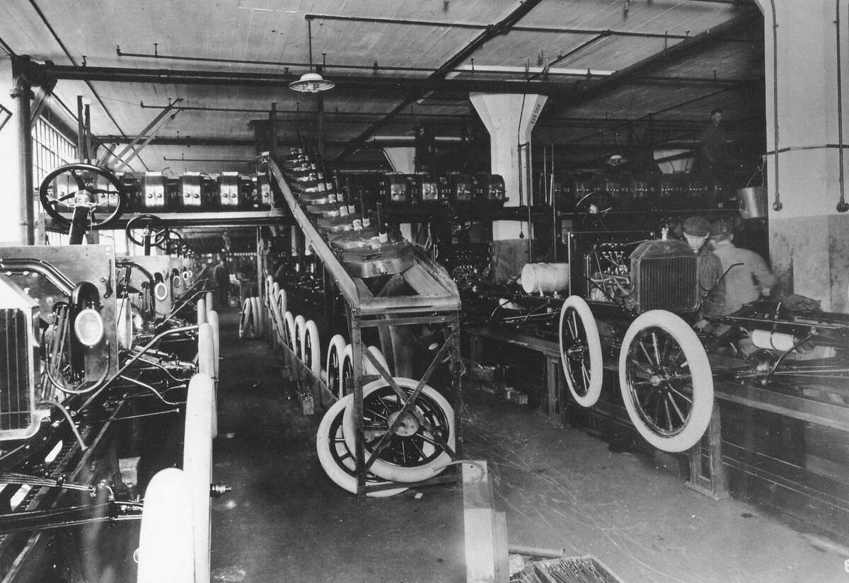 Wheels and brass radiators join the Model T chassis in the Highland Park plant in 1912.