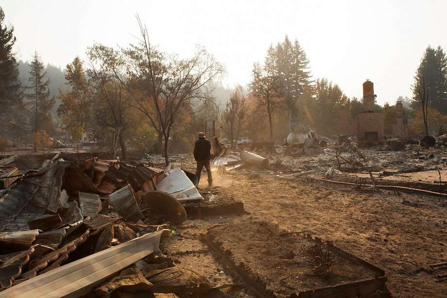 Brandon Hays, top, walks through thick ash behind his parents' home on Shallow Creek Drive in Santa Rosa. He said he spent six hours with garden hoses trying to save the home. Above: Santa Rosa firefighter Jessie Taintor prepares to fight the Tubbs Fire in the Oakmont area. Photo: Alex Washburn, The Chronicle
