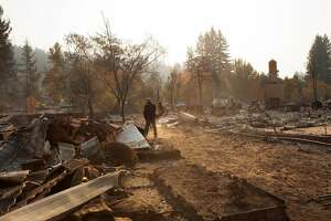 Brandon Hays walks through thick ash behind his parents home on Shallow Creek Drive in Santa Rosa, Ca. on Wednesday, October 11, 2017. Hayes estimates he spent 6 hours with garden hoses trying to save the home but was ultimately un-successful.