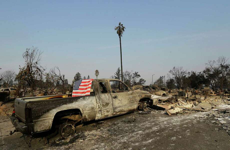 A flag is draped on the back of a truck destroyed by fires in Santa Rosa, Calif., Wednesday, Oct. 11, 2017. Wildfires tearing through California's wine country continued to expand Wednesday, destroying hundreds more homes and structures and prompting new evacuation orders. (AP Photo/Jeff Chiu) Photo: Jeff Chiu, STF / Copyright 2017 The Associated Press. All rights reserved.