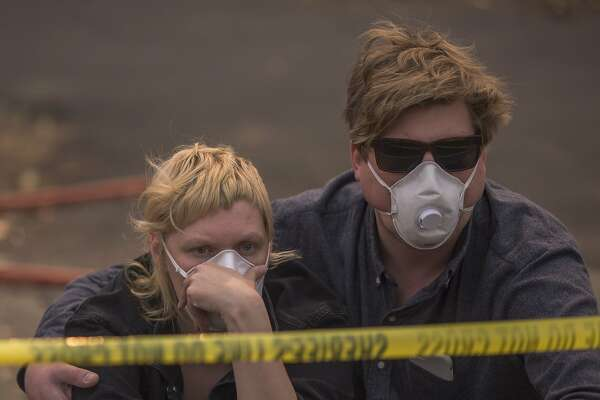 NAPA, CA -OCTOBER 11: A couple waits in vain to be escorted to pick up possessions from their home inside an evacuation zone on October 11, 2017 in Napa, California. Escorts to were called for the rest of the day due to lack of available officers. In one of the worst wildfires in state history, more than 2,000 homes have burned and  at least 21 people were killed as more than 14 wildfires continue to spread with little containment in eight Northern California counties.   (Photo by David McNew/Getty Images)
