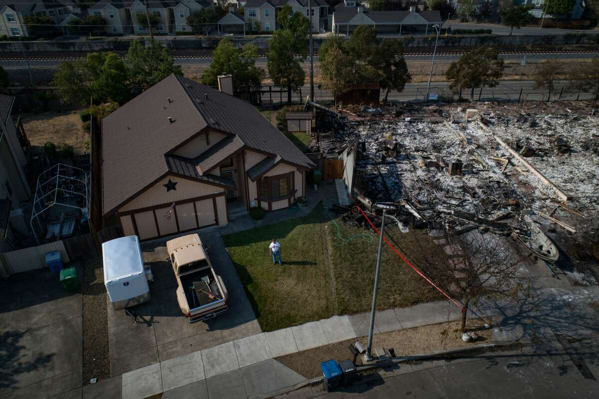 Wayne Sims stands outside his home, one of the few that escaped destruction by wildfire in the Coffey Park neighborhood of Santa Rosa, Calif., Oct. 11, 2017.