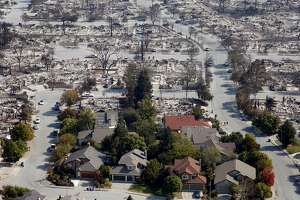 Homes that appear undamaged by Sunday night's firestorm remain near others that burned to the ground in the Coffey Park neighborhood in Santa Rosa, Calif. on Wednesday Oct. 11, 2017.