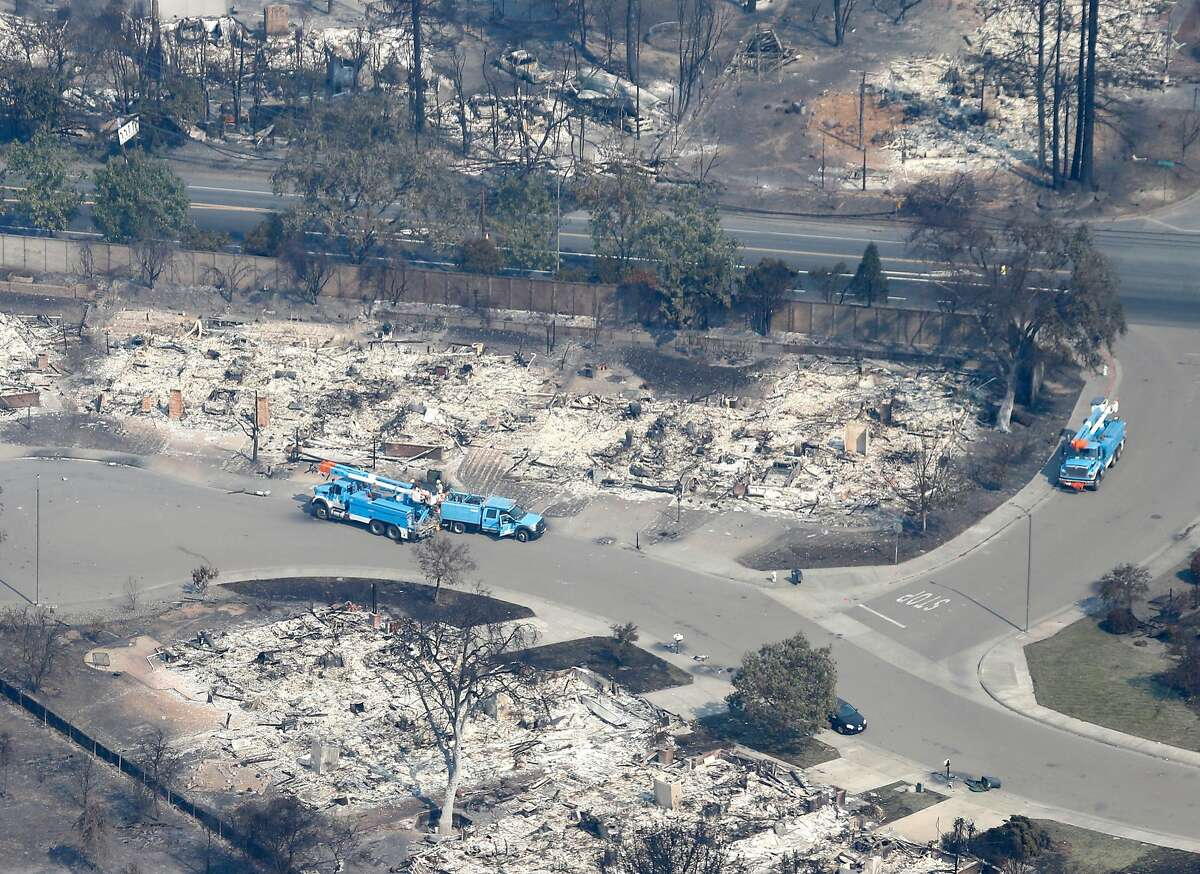PG&E crews work to restore power to a neighborhood destroyed by Monday morning's firestorm in Santa Rosa, Calif. on Wednesday Oct. 11, 2017.