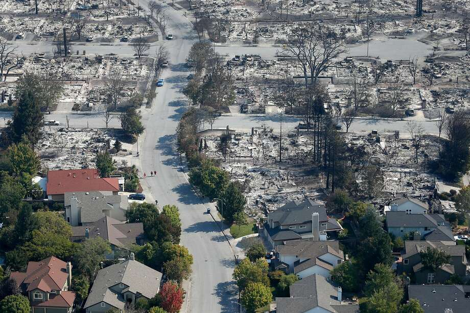 Homes that appear undamaged by Monday morning's firestorm stand near others that burned to the ground in the Coffey Park neighborhood in Santa Rosa after the Wine Country fires. Photo: Paul Chinn, The Chronicle