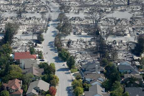 Homes that appear undamaged by Monday morning's firestorm remain near others that burned to the ground in the Coffey Park neighborhood in Santa Rosa, Calif. on Wednesday Oct. 11, 2017.