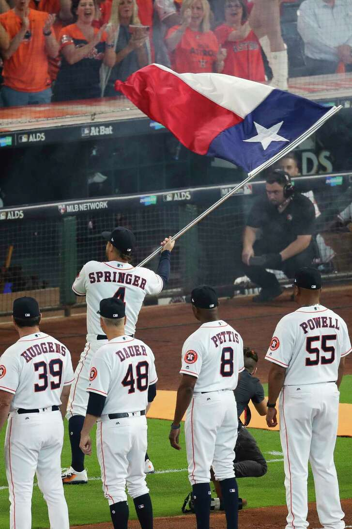 Houston Astros center-fielder George Springer runs onto the field with the Texas flag before the Houston Astros take on the Boston Red Sox at Minute Maid Park on Oct. 5. ( Michael Ciaglo / Houston Chronicle)