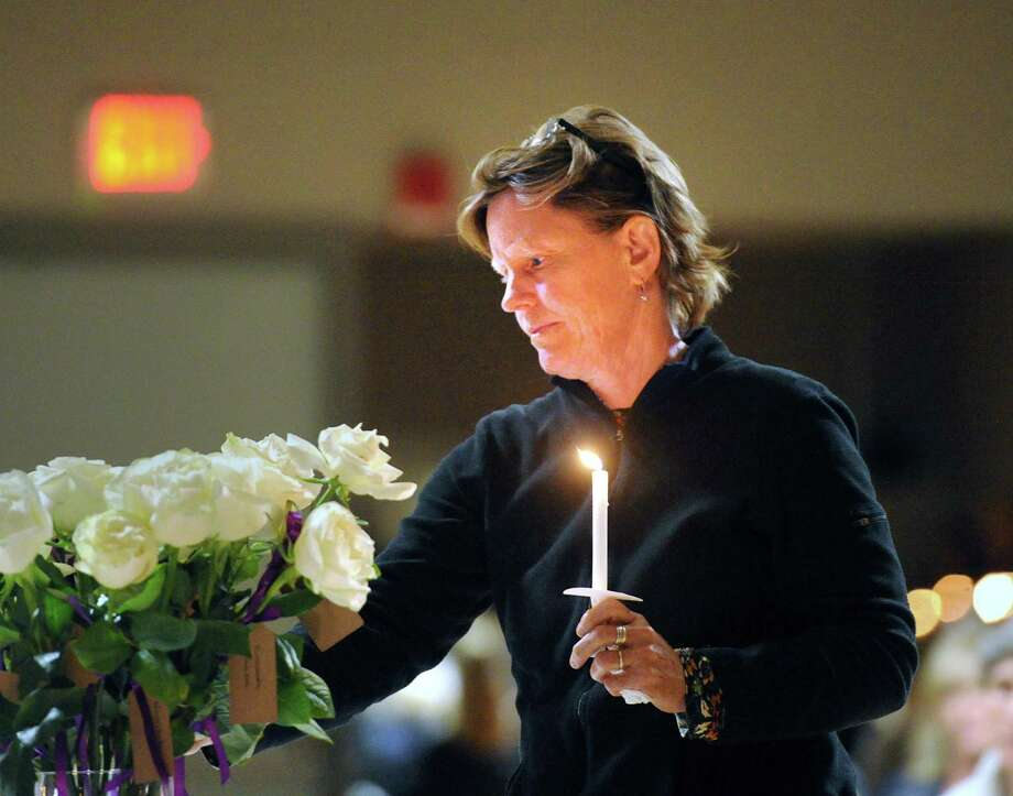 Sally Colman, of East Montpelier, Vermont, laid down a white rose to honor a victim of domestic abuse during the YWCA of Greenwich Domestic Abuse Services annual candlelight vigil Wednesday. Photo: Bob Luckey Jr. / Hearst Connecticut Media / Greenwich Time