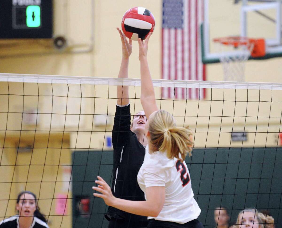 Trumbull's Krystina Schueler, left, and Amelia Bartlett (#2), right, of Greenwich, go for the ball high above the net during the girls high school volleyball match between Greenwich High School and Trumbull High School at Eastern Middle School in Greenwich, Conn., Wednesday, Oct. 11, 2017.