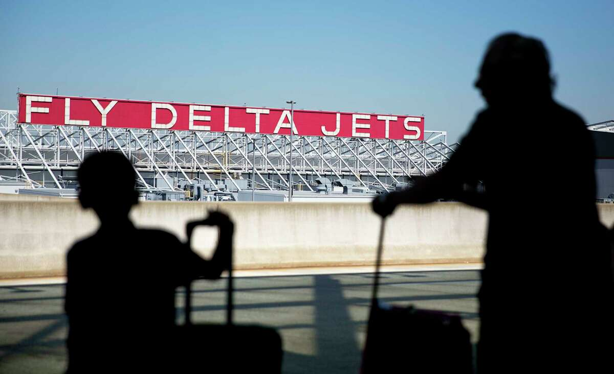 FILE - In this Thursday, Oct. 13, 2016, file photo, a Delta Air Lines sign overlooks the unloading area at Hartsfield-Jackson Atlanta International Airport, in Atlanta. Delta Air Lines, Inc. reports earnings, Wednesday, Oct. 11, 2017. (AP Photo/David Goldman, File) ORG XMIT: NYBZ303