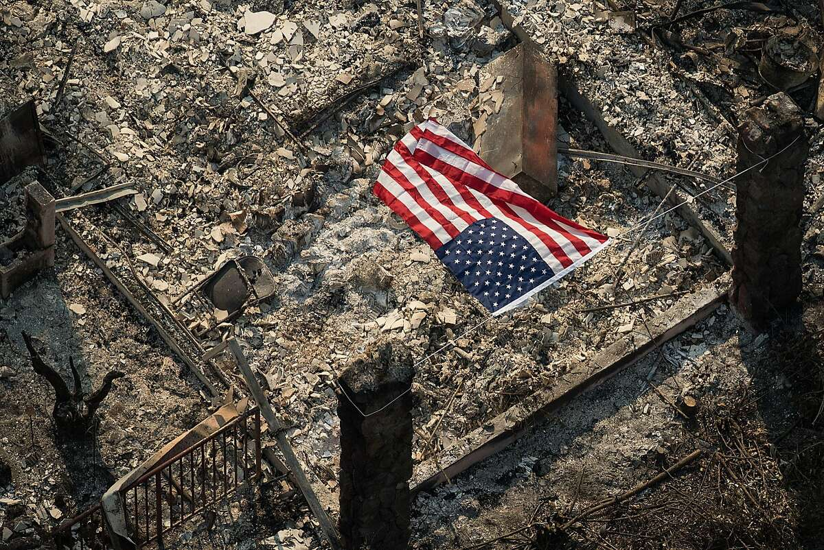 An American flag flies over the remains of a Coffey Park home following the Tubbs fire in Santa Rosa on Oct. 11, 2017.