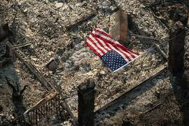 An American flag flies over the remains of a Coffey Park home following the Tubbs fire in Santa Rosa, Calif., on Wednesday, Oct. 11, 2017.