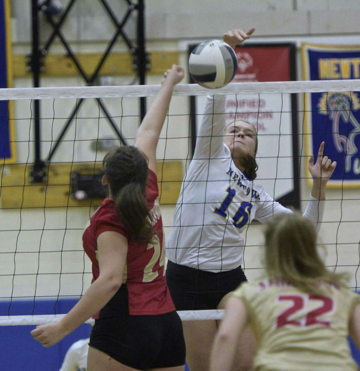 Newtown's Genevieve Murray (16) spikes the ball as Stratford's Samantha Carbone (24) goes up to try and block in the girls volleyball match between Stratford and Newtown high schools, Wednesday afternoon, October 11, 2017, at Newtown High School, in Newtown, Conn.