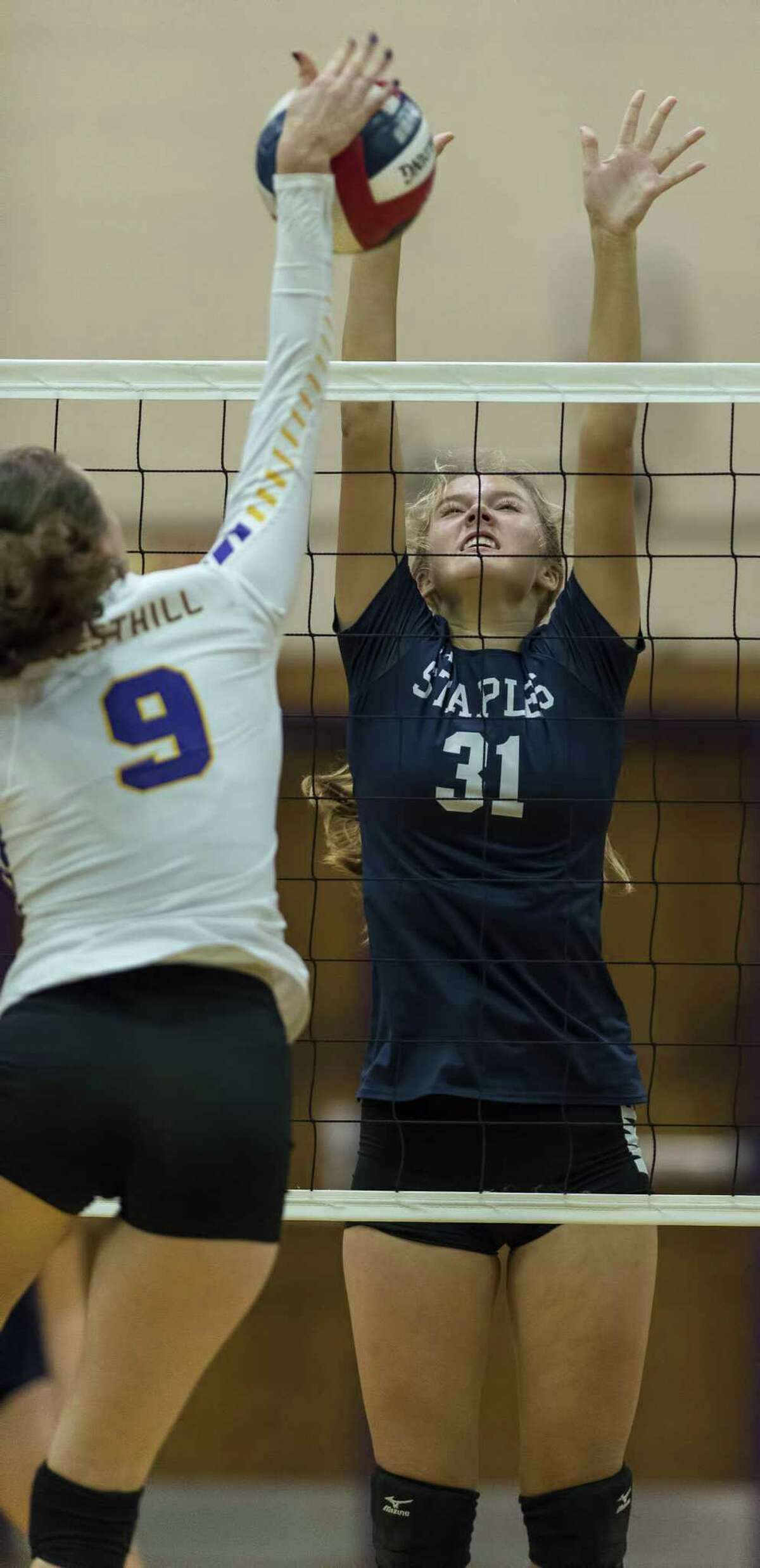 Staples High School?'s Brianna Dwyer jumps up to try to block the ball during a girls volleyball game against Westhill High School played at Westhill High School, Wednesday, October 11, 2017.