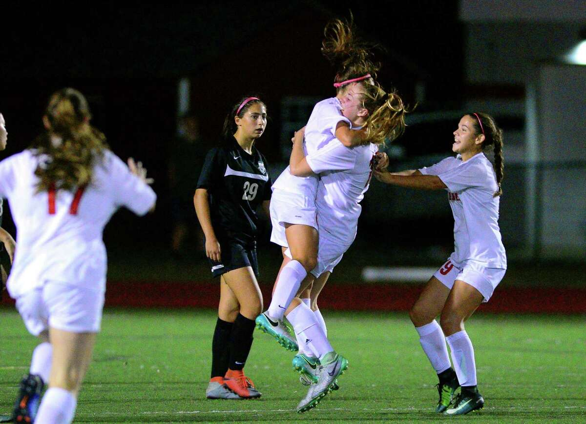 Teammates rush in to celebrate a goal by Fairfield Warde's Kaitlyn Walsh during girls soccer action against Trumbull in Fairfield, Conn., on Wednesday Oct. 11, 2017.