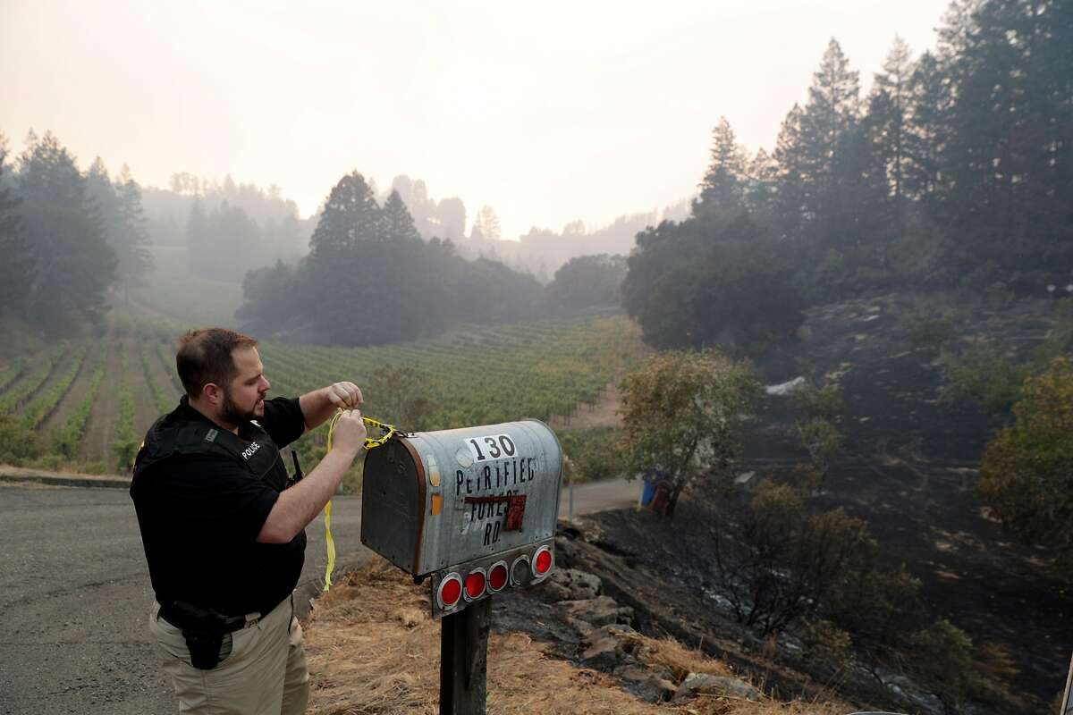 An officer with the Napa County District Attorney's office ties a piece of caution tape on a mailbox to indicate they've searched a property on Petrified Forest Road after a mandatory evacuation was called for the entire town in Calistoga, Calif., on Wednesday, October 11, 2017. The Napa and Sonoma valleys continue to be under threat from several fires not yet under control and growing fears that strong winds might worsen the situation.