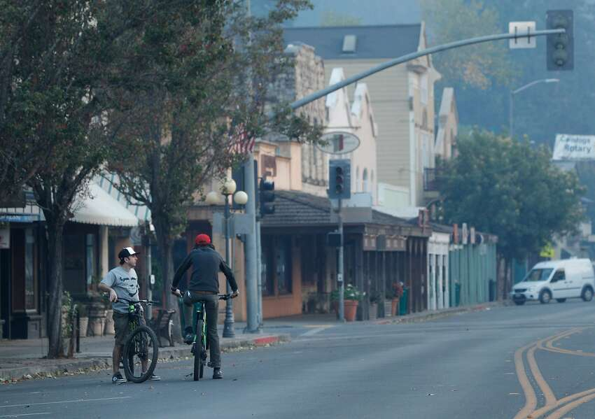 Ali Pehzadpour, left, talks in an abandoned downtown Calistoga, with Marshall Hayman, right, who lost home to the fire, after a mandatory evacuation was called for the entire town in Calistoga, Calif., on Wednesday, October 11, 2017. The Napa and Sonoma valleys continue to be under threat from several fires not yet under control and growing fears that strong winds might worsen the situation.