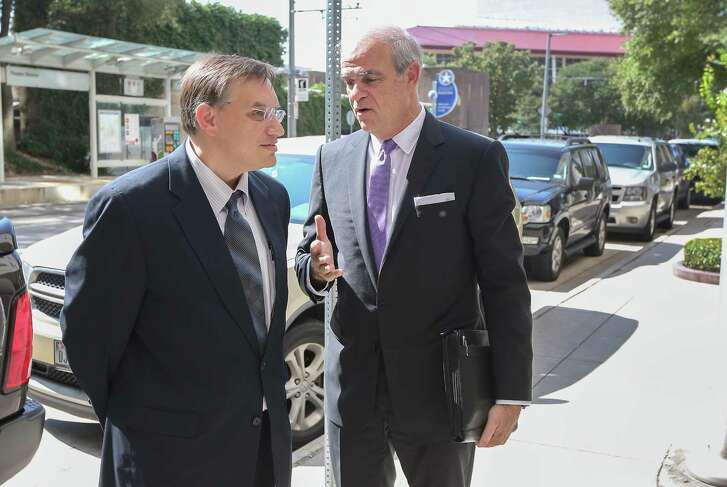 Jason Posey (left), former Rep. Steve Stockman's aide, chats his attorney Phil Hilder before entering the Bob Casey Federal Courthouse on Wednesday to plead guilty.