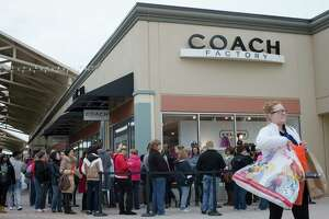 "FILE - In this Friday, Nov. 27, 2015, file photo, shoppers wait in line outside a Coach factory outlet store at the Cincinnati Premium Outlets, in Monroe, Ohio. The storied Coach brand is changing its name to Tapestry, it says to better incorporate all of the goods it sells. Coach Inc. will change its New York Stock Exchange ticker symbol from ""COH"" to ""TPR"" on Oct. 31, 2017. (AP Photo/John Minchillo, File)"