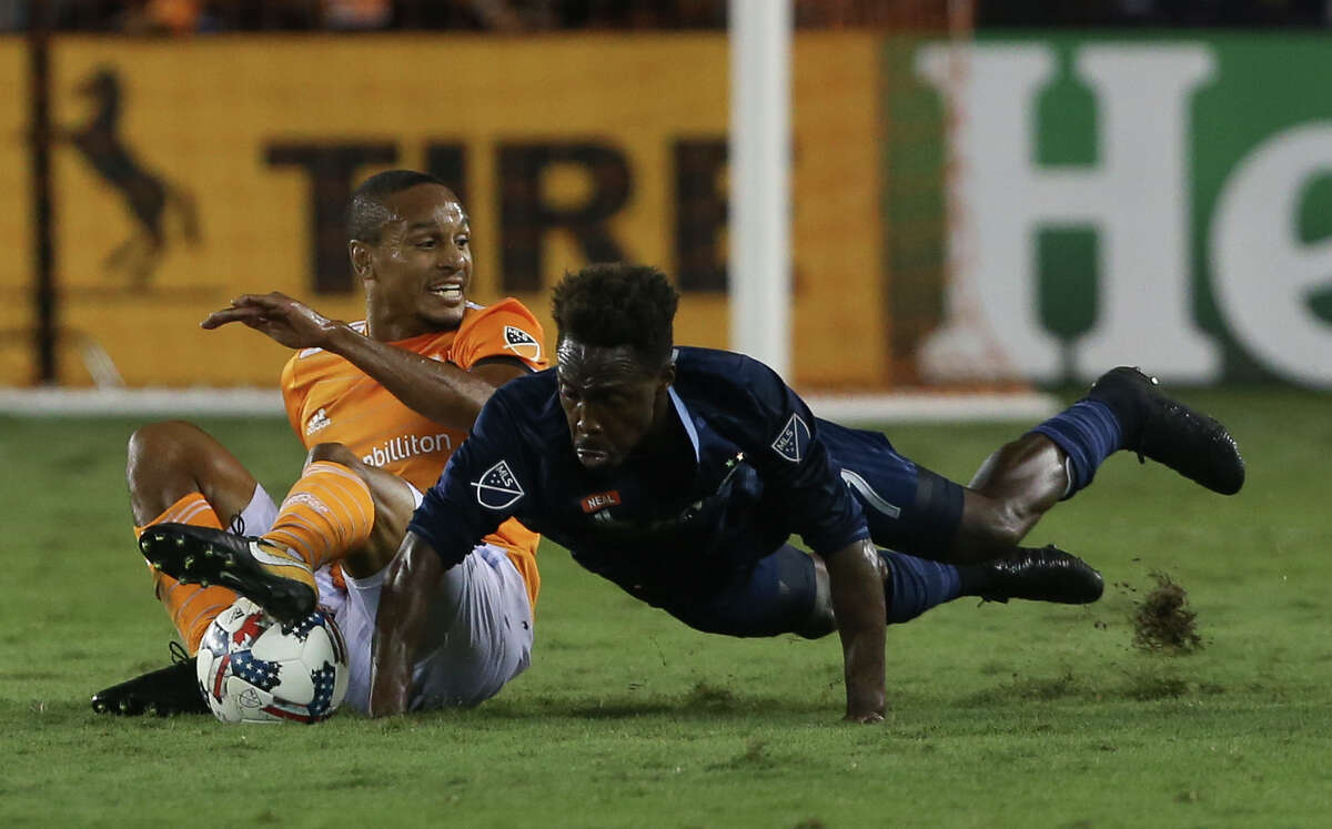 Houston Dynamo midfielder Ricardo Clark (13) and Sporting Kansas City forward Gerso Fernandes (7) fall onto the ground while battling for possession of the ball during the first half of the MLS game at BBVA Compass Stadium Wednesday, Oct. 11, 2017, in Houston. ( Yi-Chin Lee / Houston Chronicle )