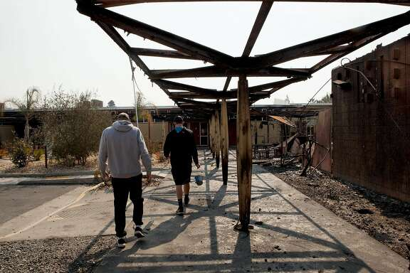 Seniors Tyler Botteri and Deric Younce (left to right) look through the damage Tubbs Fire inflicted on Cardinal Newman High School in Santa Rosa, Ca. on Wednesday, October 11, 2017. Both boys are athletes at the school.