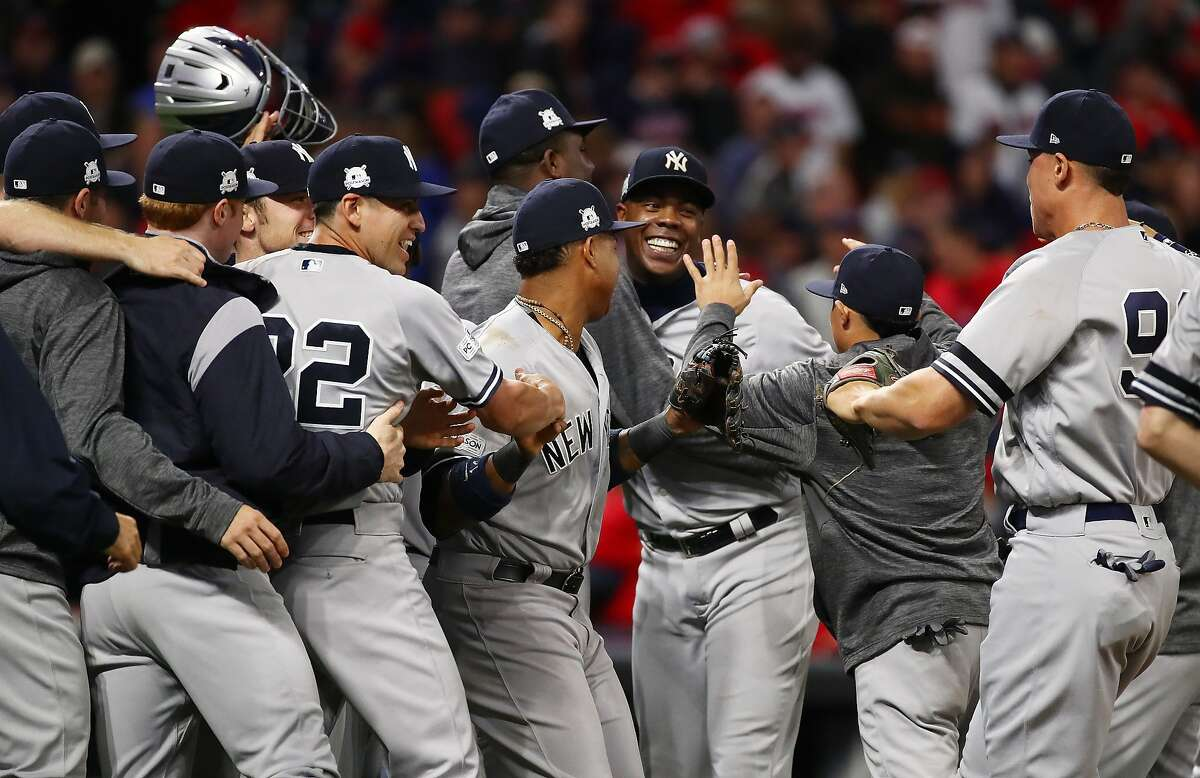 Aroldis Chapman (facing) and the Yankees exult after eliminating Cleveland from the postseason. Chapman pitched two hitless innings to pick up his second save in the ALDS.