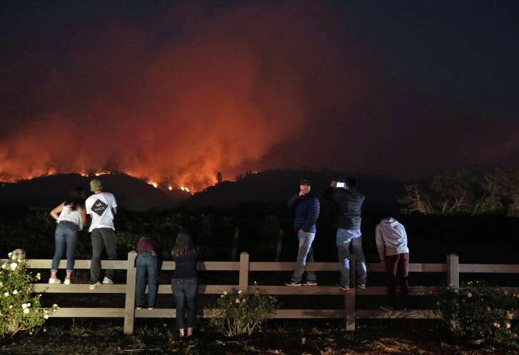 Members of the community watch as a fire grows along the ridge near Highway 12 outside Eldridge, Calif., on Tuesday, October 10, 2017. Sonoma Valley continues to be under threat from several fires as some communities begin to assess the impact of the fires.