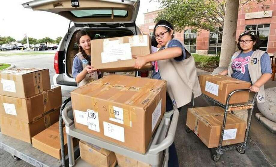 Clark Middle School Troop 9167 members Gabriela Ramirez, Ariana Sanchez and Samantha Cardenas unload boxes of cancer care packages they made for the Laredo Medical Center's A.R. Sanchez Sr. & Iris Stewart Cancer Treatment Center on Tuesday. Photo: Courtesy