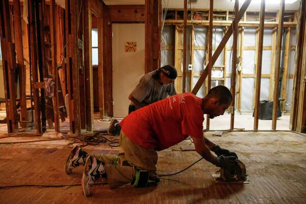 Contractor Rick Cervantes, with Alfred C. Schuley Hardwood Floors, cuts up the floors at Carolanne Norris' home that flooded during Hurricane Harvey in Kingwood. Norris believes that the release from the Lake Conroe dam is responsible for flooding her home.