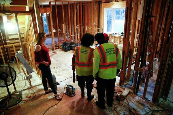 Carolanne Norris stands with FEMA investigators in her home that flooded during Hurricane Harvey in Kingwood.